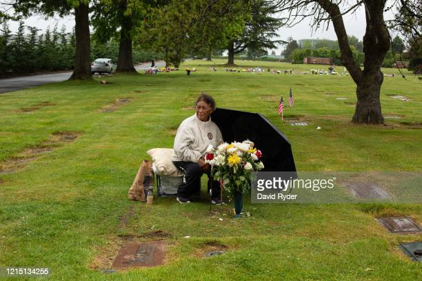 Lala TaAmilo sits at the grave site of her late husband Tupuono Sione TaAmilo after singing for him on Memorial Day at Washington Memorial Park on...