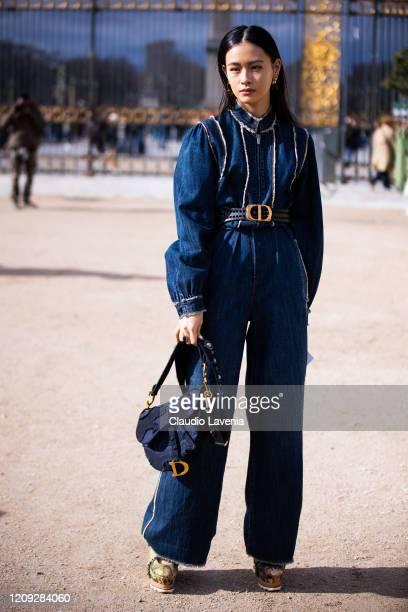 Lala Takahashi, wearing a denim jumpsuit, Dior belt and Dior bag, is seen outside Dior, during Paris Fashion Week - Womenswear Fall/Winter 2020/2021...