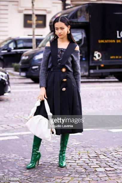 Lala Takahashi, wearing a grey cardigan, black skirt overall, white bag and green boots, is seen outside Miu Miu, during Paris Fashion Week -...
