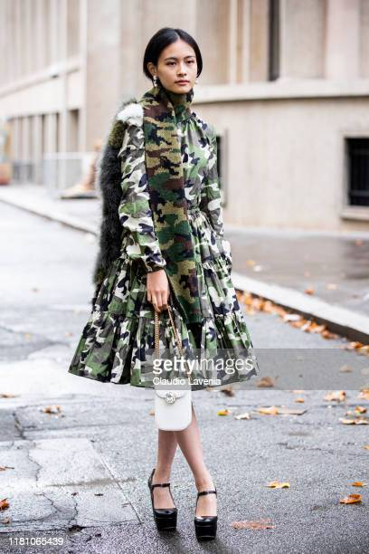 Lala Takahashi wearing a military print dress military print scarf black heels and white bag is seen outside the Miu Miu show during Paris Fashion...