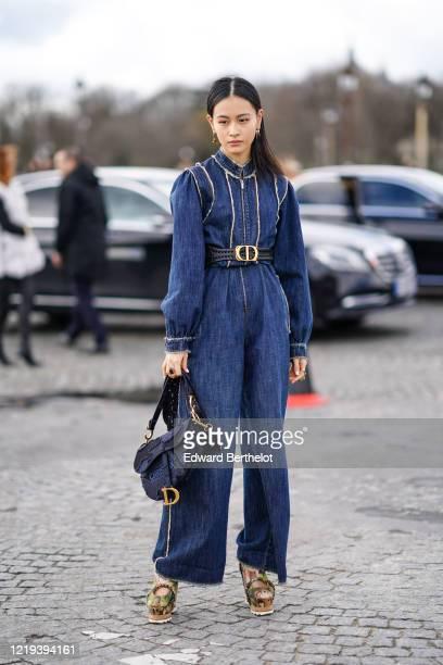 Lala Takahashi wears a blue denim jumpsuit, a Dior belt, a Dior Saddle bag, platform shoes, outside Dior, during Paris Fashion Week - Womenswear...