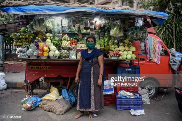 Lalita Kesharwani vegetable vendor, poses for a picture in front of her stall during a government-imposed nationwide lockdown as a preventive measure...