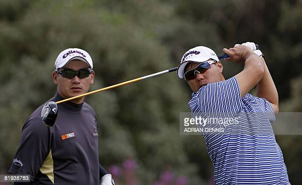 Lam ChihBing of Singapore drives off the 2nd hole as Angelo Que of Phillipines looks on during the second practice day at the British Open golf...