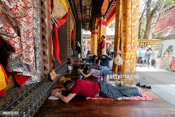 Lama Monks and tourists prostrate themselves in front of the main hall Kumbum Monastery is one of the two most important Tibetan Buddhist monasteries...