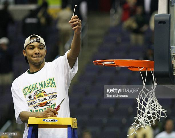 Lamar Butler of the George Mason Patriots cuts down the net after defeating the Connecticut Huskies in overtime during the Regional Finals of the...