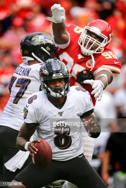 Lamar Jackson of the Baltimore Ravens avoids the pass rush of Chris Jones of the Kansas City Chiefs in the fourth quarter at Arrowhead Stadium on...