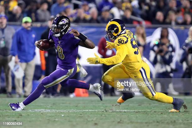 Lamar Jackson of the Baltimore Ravens eludes the defense of Samson Ebukam of the Los Angeles Rams during the second half of a game at Los Angeles...