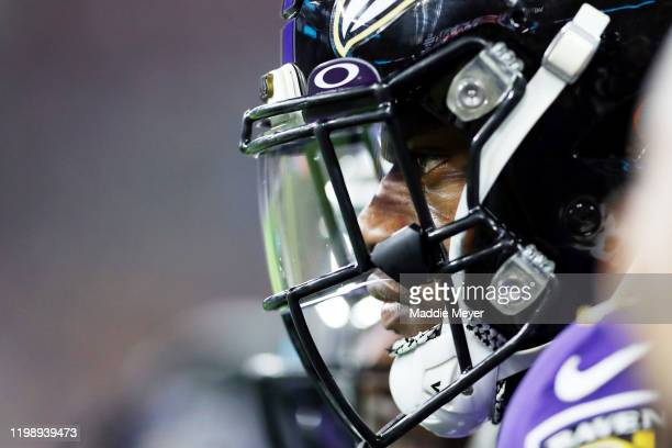 Lamar Jackson of the Baltimore Ravens looks on from the sideline during the first half against the Tennessee Titans in the AFC Divisional Playoff...