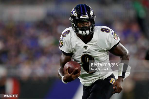 Lamar Jackson of the Baltimore Ravens runs with the ball in the first half of a preseason game against the Green Bay Packers at MT Bank Stadium on...