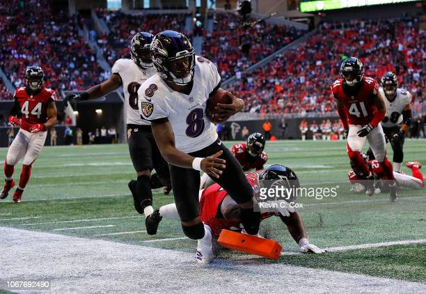 Lamar Jackson of the Baltimore Ravens rushes for a touchdown past Grady Jarrett of the Atlanta Falcons at MercedesBenz Stadium on December 2 2018 in...