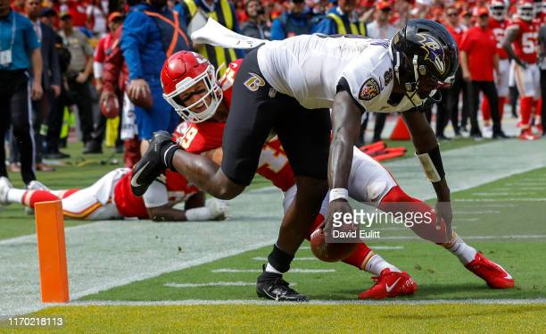 Lamar Jackson of the Baltimore Ravens scores a touchdown late in the fourth quarter past the missed tackle of Daniel Sorensen of the Kansas City...