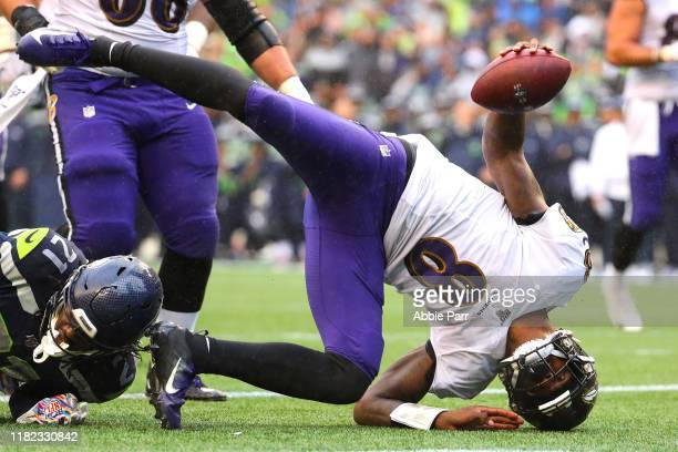 Lamar Jackson of the Baltimore Ravens scores an eight yard touchdown against the Seattle Seahawks in the third quarter during their game at...