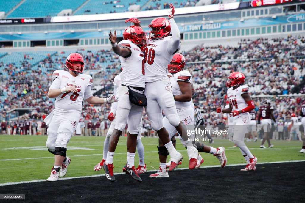 Lamar Jackson #8 of the Louisville Cardinals celebrates with teammate Charles Standberry #80 after running for a touchdown in the first half of the TaxSlayer Bowl against the Mississippi State Bulldogs at EverBank Field on December 30, 2017 in Jacksonville, Florida.