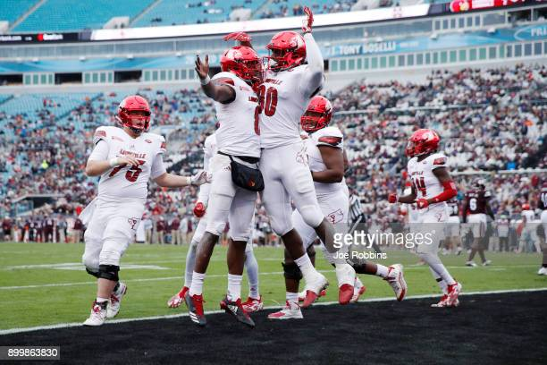 Lamar Jackson of the Louisville Cardinals celebrates with teammate Charles Standberry after running for a touchdown in the first half of the...