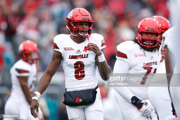 Lamar Jackson of the Louisville Cardinals directs the offense in the first half of the TaxSlayer Bowl against the Mississippi State Bulldogs at...