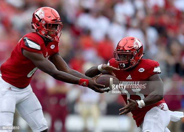 Lamar Jackson of the Louisville Cardinals hands it off to Brandon Radcliff during the game against the Florida State Seminoles at Papa John's...