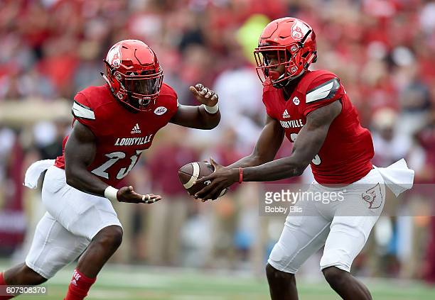 Lamar Jackson of the Louisville Cardinals hands the ball off to Brandon Radcliff of the Louisville Cardinals during the first quarter of the game...