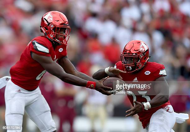 Lamar Jackson of the Louisville Cardinals hands the ball off to Brandon Radcliff of the Louisville Cardinals during the game against the Florida...