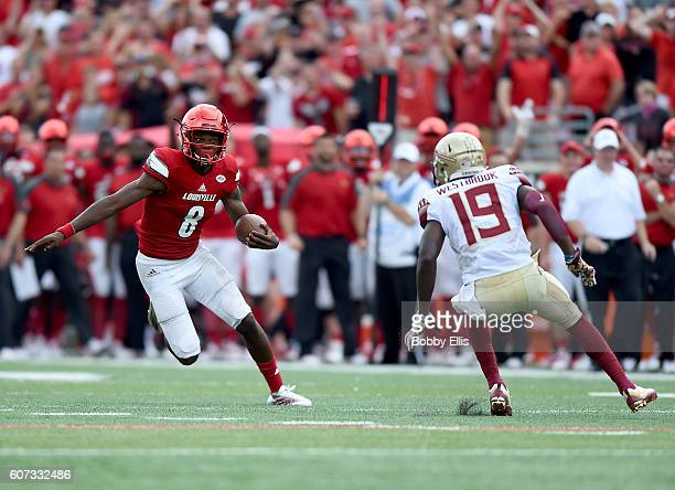 Lamar Jackson of the Louisville Cardinals runs past AJ Westerbrook of the Florida State Seminoles duriing the fourth quarter of the game at Papa...