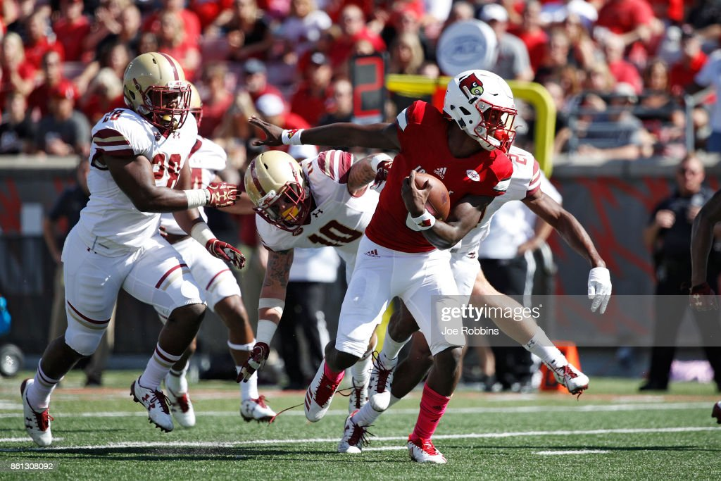 Lamar Jackson #8 of the Louisville Cardinals runs past Ty Schwab #10 and Sharrieff Grice #26 of the Boston College Eagles on his way to a 20-yard touchdown run in the first quarter of a game at Papa John's Cardinal Stadium on October 14, 2017 in Louisville, Kentucky.