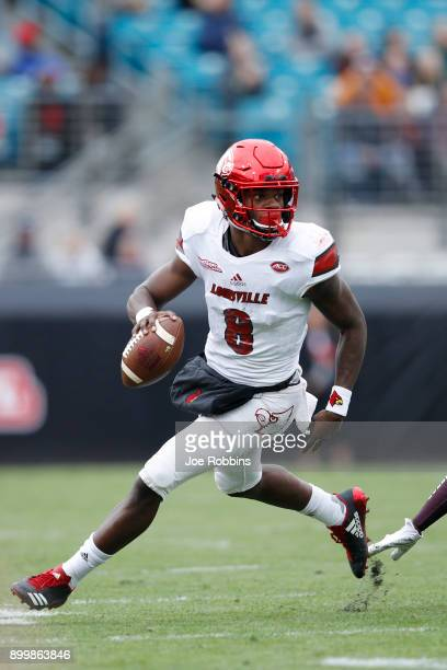 Lamar Jackson of the Louisville Cardinals runs the ball in the first half of the TaxSlayer Bowl against the Mississippi State Bulldogs at EverBank...