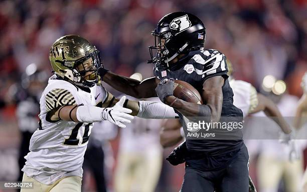 Lamar Jackson of the Louisville Cardinals runs with the ball while defended by Amari Henderson of the Wake Forest Deamon Deacons at Papa John's...
