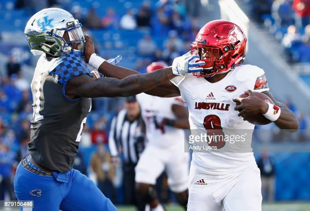 Lamar Jackson of the Louisville Cardinals runs with the ball while defended by Chris Westry of the Kentucky Wildcats during the game at Commonwealth...