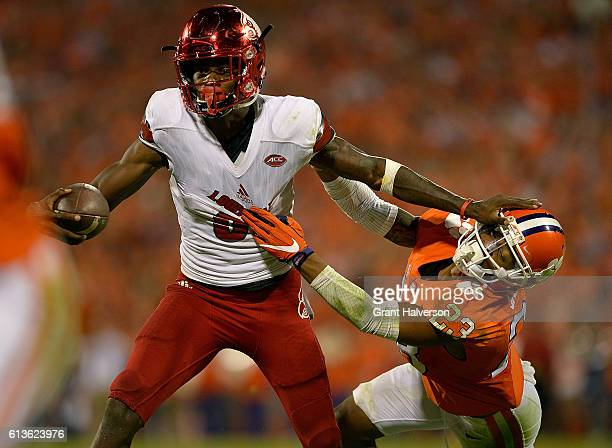 Lamar Jackson of the Louisville Cardinals stiffarms Van Smith of the Clemson Tigers during the game at Memorial Stadium on October 1 2016 in Clemson...