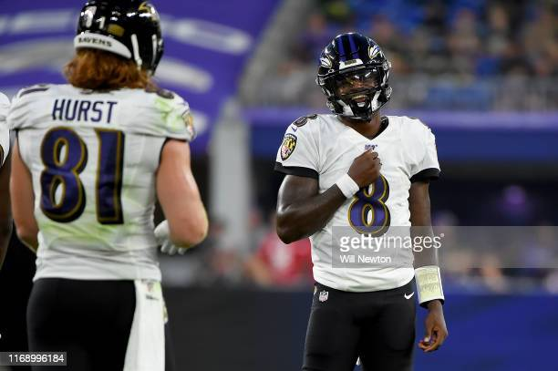 Lamar Jackson reacts to Hayden Hurst of the Baltimore Ravens after a play against the Green Bay Packers during the first half of a preseason game at...