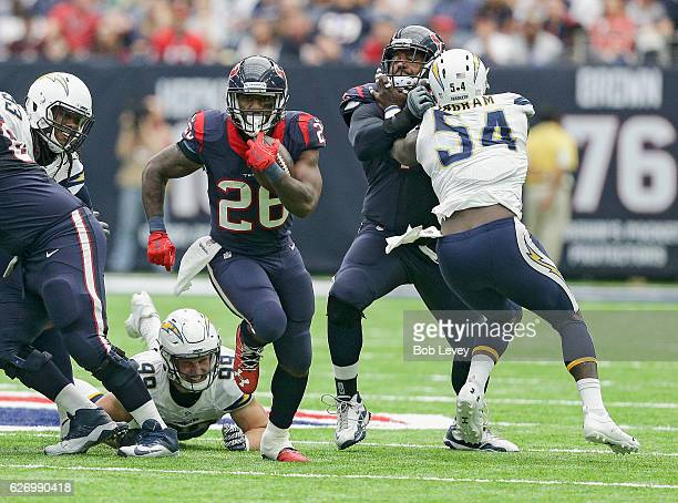 Lamar Miller of the Houston Texans avoids the tackle by Joey Bosa of the San Diego Chargers as Duane Brown blocks Melvin Ingram at NRG Stadium on...