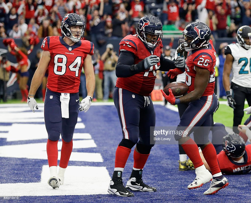 Lamar Miller #26 of the Houston Texans celebrates with Duane Brown #76 and Ryan Griffin #84 after scoring on a one yard run against the Jacksonville Jaguars at NRG Stadium on December 18, 2016 in Houston, Texas.