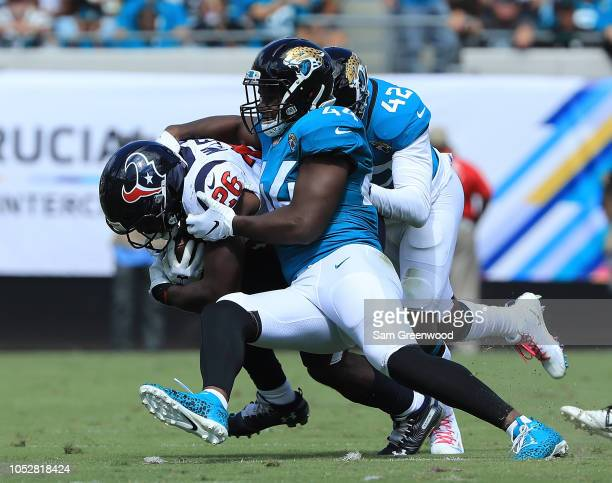 Lamar Miller of the Houston Texans is tackled by Barry Church and Myles Jack of the Jacksonville Jaguars during the game at TIAA Bank Field on...