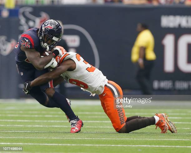 Lamar Miller of the Houston Texans is tackled by T.J. Carrie of the Cleveland Browns at NRG Stadium on December 02, 2018 in Houston, Texas.