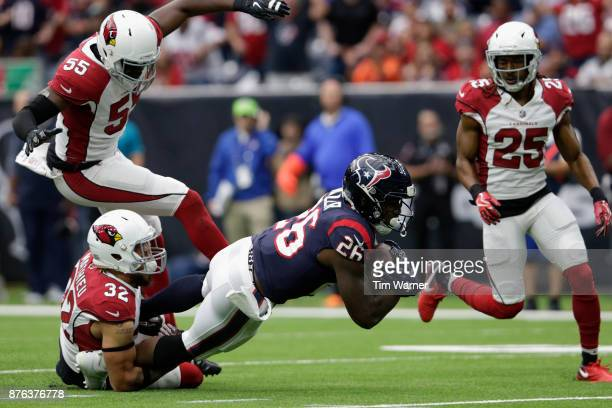 Lamar Miller of the Houston Texans is tackled by Tyrann Mathieu of the Arizona Cardinals in the second quarter at NRG Stadium on November 19 2017 in...