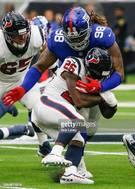 Lamar Miller of the Houston Texans is wrapped up by Damon Harrison of the New York Giants in the first quarter at NRG Stadium on September 23 2018 in...