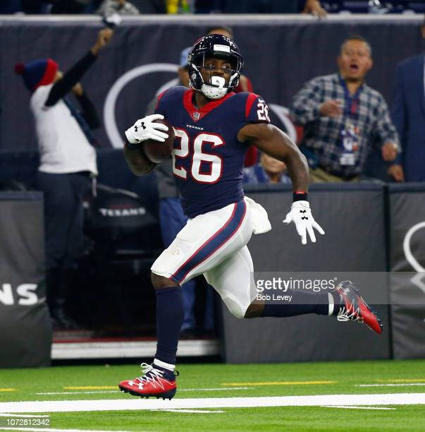 Lamar Miller of the Houston Texans looks back as he runs for a 97 yard touchdown during the second quarter against the Tennessee Titans at NRG...