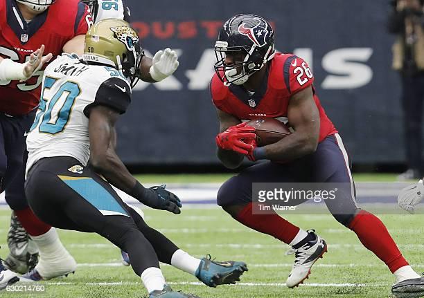 Lamar Miller of the Houston Texans runs the ball against Telvin Smith of the Jacksonville Jaguars in the third quarter at NRG Stadium on December 18...