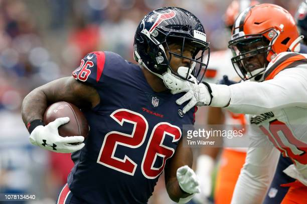 Lamar Miller of the Houston Texans runs the ball defended by Emmanuel Ogbah of the Cleveland Browns in the first quarter at NRG Stadium on December 2...