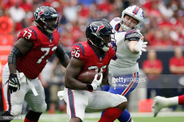 Lamar Miller of the Houston Texans runs the ball defended by Harrison Phillips of the Buffalo Bills in the second half at NRG Stadium on October 14,...