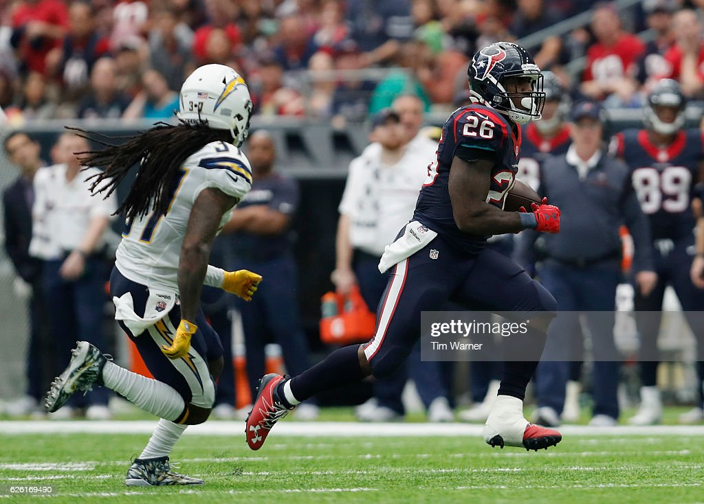 Lamar Miller #26 of the Houston Texans runs the ball defended by Jahleel Addae #37 of the San Diego Chargers in the third quarter at NRG Stadium on November 27, 2016 in Houston, Texas.