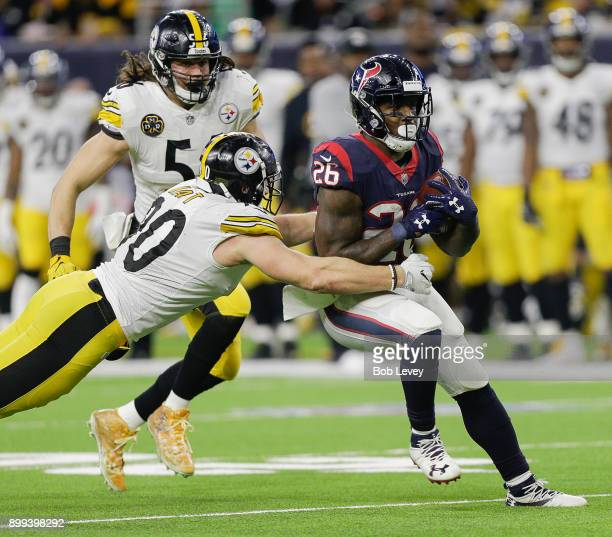 Lamar Miller of the Houston Texans runs with the ball past Anthony Chickillo of the Pittsburgh Steelers and TJ Watt during game action at NRG Stadium...