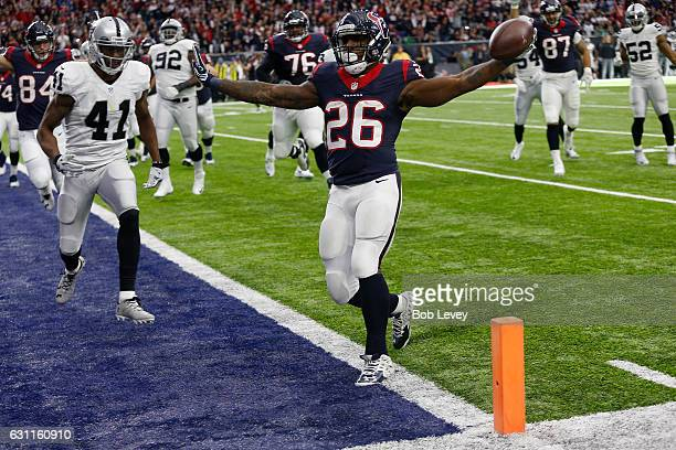 Lamar Miller of the Houston Texans rushes for a touchdown during the first quarter against the Oakland Raiders in their AFC Wild Card game at NRG...