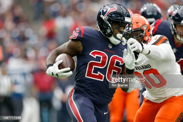 Lamar Miller of the Houston Texans rushes the ball defended by Emmanuel Ogbah of the Cleveland Browns in the first quarter at NRG Stadium on December...