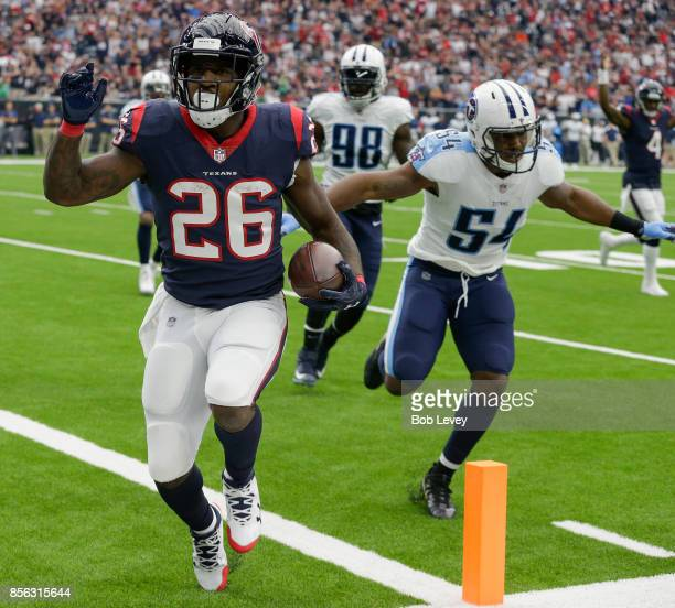 Lamar Miller of the Houston Texans scores on a two yard run in the first quarter as he beats Avery Williamson of the Tennessee Titans to he endzone...