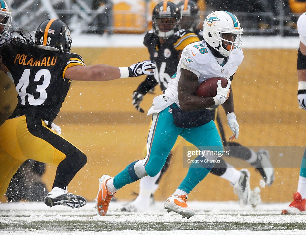 Lamar Miller #26 of the Miami Dolphins avoids the reach of Troy Polamalu #43 of the Pittsburgh Steelers at Heinz Field on December 8, 2013 in Pittsburgh, Pennsylvania. Miami won the game 34-28.