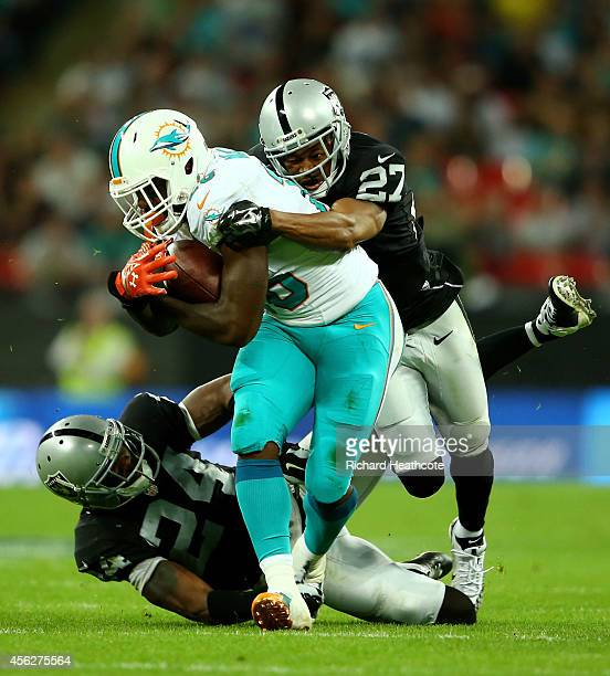 Lamar Miller of the Miami Dolphins is tackled by Charles Woodson of the Oakland Raiders and Carlos Rogers of the Oakland Raiders during the NFL match...