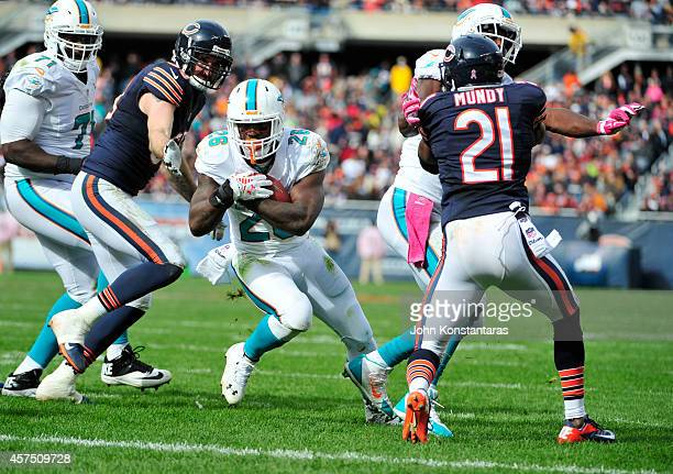 Lamar Miller of the Miami Dolphins runs by Ryan Mundy of the Chicago Bears for a touchdown during the third quarter of the game at Soldier Field on...