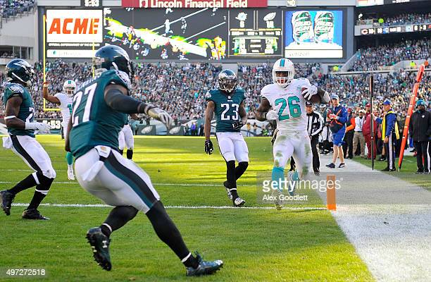 Lamar Miller of the Miami Dolphins scores a second quarter touchdown reception against Malcolm Jenkins and Nolan Carroll of the Philadelphia Eagles...