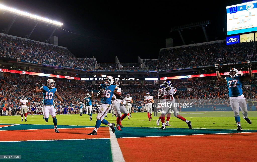 Lamar Miller #26 of the Miami Dolphins scores a touchdown during the first quarter of the game against the New York Giants at Sun Life Stadium on December 14, 2015 in Miami Gardens, Florida.