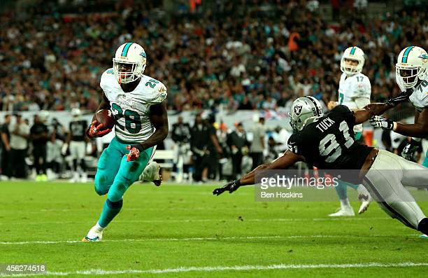 Lamar Miller of the Miami Dolphins scores his team's fourth touchdown on a one yard run during the NFL match between the Oakland Raiders and the...